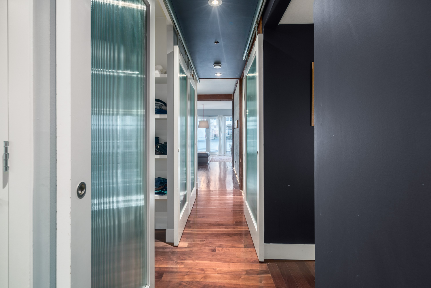 Alluring hallway reveals rustic style barn doors, concrete walls set off with rich walnut floors